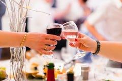 Mani femminili con un tintinnio due di vetro di vino Fotografia Stock Libera da Diritti