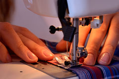 Mani femminili del primo piano che cucono tessuto sulla macchina per cucire Fotografia Stock