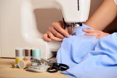 Mani femminili del primo piano che cucono tessuto sulla macchina per cucire Fotografia Stock Libera da Diritti