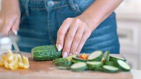 Mani femminili del primo piano che tagliano le verdure fresche di estate facendo uso del coltello che cucinano insalata vegetaria stock footage