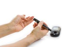 Mani femminili del primo piano facendo uso dell'analizzatore di glucometer Immagine Stock