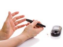Mani femminili del primo piano facendo uso dell'analizzatore di glucometer Fotografia Stock Libera da Diritti