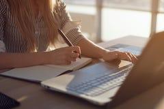 Mani femminili delle free lance della donna con scrittura della penna sul taccuino a casa o sull'ufficio Immagine Stock Libera da Diritti