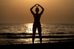 Mani femminili delle siluette che fanno una forma del cuore Immagini Stock Libere da Diritti
