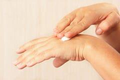 Mani femminili facendo uso della crema di pelle antinvecchiamento Fotografia Stock Libera da Diritti