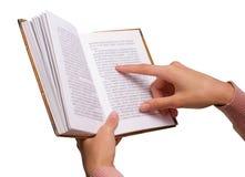 Mani femminili isolate che tengono un libro d'annata, indicante su una parola Fotografia Stock