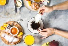 Mani femminili La prima colazione è servito con caffè, succo d'arancia, i croissant ed i frutti su fondo concreto immagine stock