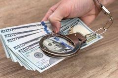 mani femminili in manette con i dollari Fotografia Stock