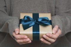 Mani femminili in scatola della tenuta del maglione avvolta in carta del mestiere con il nastro blu Fotografie Stock