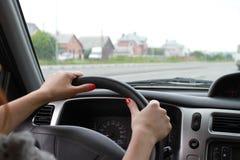 Mani femminili su una ruota di automobile Fotografia Stock