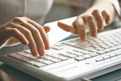 Mani femminili sulla tastiera bianca. Fotografia Stock Libera da Diritti