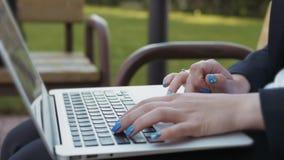 Mani femminili sulla tastiera del computer portatile - donna che scrive sul primo piano del taccuino all'aperto stock footage