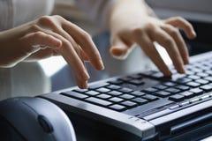 Mani femminili sulla tastiera nera. Immagine Stock