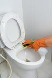Mani in guanti arancio che puliscono WC, toilette, lavabo fotografia stock libera da diritti
