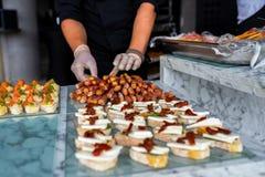 Mani in guanti con alimento sulla tavola di banchetto fotografie stock libere da diritti