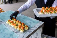 Mani in guanti con alimento sulla tavola di banchetto fotografia stock