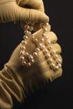 Mani inguantate che giocano con una serie di perle Fotografia Stock