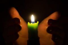 Mani intorno alla candela fotografia stock libera da diritti