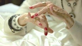 Mani invecchiate della donna con gli anelli di lusso stock footage