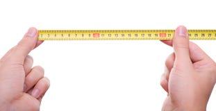 Mani isolate che misurano dalla misura di nastro Fotografie Stock Libere da Diritti