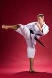 Mani in karate kimono kicking stock photography