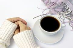 Mani in maglione bianco vicino alla tazza di caffè ceramica ed al plaid tricottato rosa che si trovano sulla tavola bianca, spazi fotografie stock