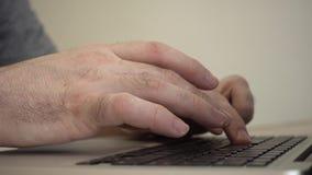 Mani maschii che digitano su una tastiera del computer portatile stock footage