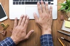 Mani maschii che funzionano con il computer portatile moderno sulla tavola della scrivania immagini stock libere da diritti