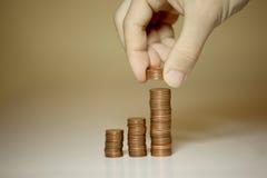 Mani maschii che impilano soldi Fotografie Stock