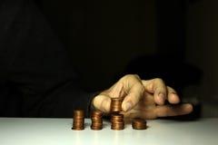 Mani maschii che impilano soldi ai mucchi Fotografia Stock
