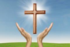 Mani maschii che pregano con un incrocio di legno Fotografia Stock Libera da Diritti