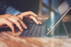 Mani maschii che scrivono sulla stazione elettronica del tastiera-bacino della compressa Equipaggi il lavoro all'ufficio mentre s fotografie stock libere da diritti