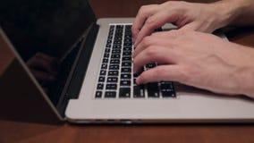 Mani maschii che scrivono sulla tastiera del computer portatile archivi video