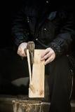 Mani maschii che tagliano plancia a pezzi con l'ascia Immagine Stock