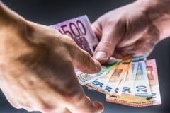 Mani maschii che tengono le euro banconote e l'altra mano per ricevere un dono fotografie stock libere da diritti