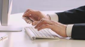 Mani maschii che tengono una carta di credito alla tastiera durante l'acquisto online archivi video