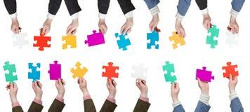 Mani maschii con differenti pezzi di puzzle Fotografia Stock