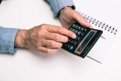 Mani maschii con il calcolatore ed il blocco note sul ripiano del tavolo bianco fotografia stock