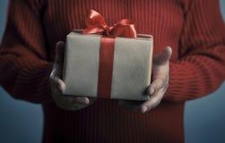 Mani maschii con il contenitore di regalo rosso dell'arco Fotografia Stock Libera da Diritti
