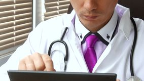 Mani maschii del ` s di medico facendo uso del suo computer digitale moderno della compressa stock footage