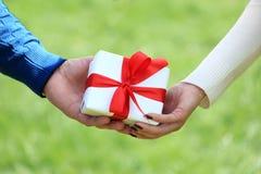 Mani maschii e femminili con il contenitore di regalo fotografie stock libere da diritti