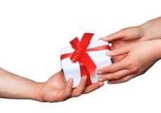 Mani maschii e femminili con il contenitore di regalo bianco con l'arco Immagini Stock