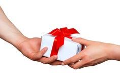 Mani maschii e femminili con il contenitore di regalo bianco con l'arco sopra bianco Immagini Stock Libere da Diritti