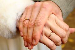 Mani maschii e femminili con le fedi nuziali immagine stock