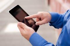 Mani maschii facendo uso della compressa digitale Fotografia Stock