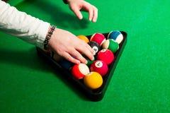 Mani maschii per disporre le palle nel triangolo per giocare palla otto Fotografia Stock