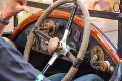 Mani maschii sul volante classico d'annata dell'automobile Immagini Stock