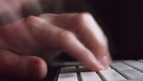 Mani maschii sulla tastiera di computer nella stanza scura, battitura a macchina veloce stock footage