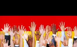 Mani multietniche sollevate e bandiera tedesca Fotografia Stock