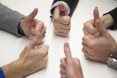 Mani multiple che danno i pollici su fotografie stock
